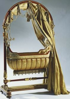 Swinging-cradle 1840 A mahogany and parcel-gilt swinging-cradle with an arched superstructure with draped replacement silk curtains; the boat-shaped cradle with a ribbed frame-work suspended from ormolu brackets at either end; turned stretcher above an upholstered foot-rest.