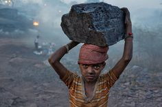 Photo by Robb Kendrick via National Geographic PROOF: Jharkhand, India. A young boy carries  a chunk of coal into the mining camp where he lives.