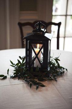 Lantern centrepiece with greenery. Photo by Paige Winn Photography (via MyWedding.com).