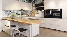 Moderní hladké kuchyni kontrastuje přírodní dřevěná deska. Spolu s fotografií stromu na stěnách a s černými doplňky tvoří harmonický celek. Kuchyně Sykora.
