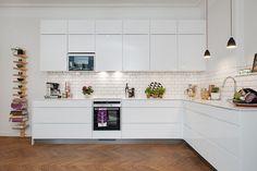cuisine en L blanche et élégante avec une crédence en carreaux métro blancs