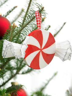 Turn a plain papier-mache disk into an ornament that mimics peppermint candy. Paint the disk white; let dry. Then paint red swirls; let dry. Apply two or three coats of glaze, letting it dry between coats. Apply silver glitter to the edges of two cupcake liners, fold each liner in half, then accordion-fold each. Hot-glue a liner to each side of the ornament. Add a ribbon hanger with hot glue.