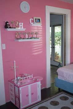 """The girls' trophy shelves (awards from karate and soccer), Target clock and Target.com baby doll care center. The door to the kids' bathroom had to be partially obscured to make room for the girls' dream beds (they previously had a bunk bed but each begged for a """"real bed"""" so Mommy could properly tuck them in...)"""