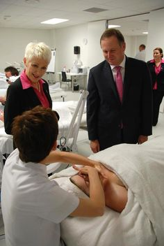 Brenda demonstrating a facial massage with Principal Catherine Wouters and Prime Minister John Key talking to her.  Kerryn Fletcher is in the background.