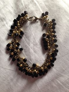 Black and gold beaded charm bracelet on antique chain!   Price: £5  Warning: Please keep this bracelet dry at all times! Do not wear it in the shower or continuous water use!