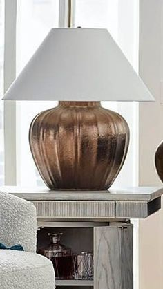 The body of our curvy ceramic lamp is crafted of hand-thrown clay that has been kiln dried and given a bronze powdercoated finish for a slightly metallic appearance. It's topped with an ivory linen shade and a metal finial.