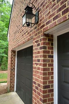 dark garage door and red brick house