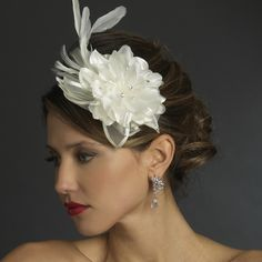 "The ivory side accented flower bridal headband is a beautiful silver side-accent headband with delicate detailing. A floral fabric side ornament of tulle and satin petals is decorated with Swarovski rhinestones, pearls and feathers with bursts of sparkling genuine crystals! Size: Design extends 9"" long by 5"" wide on 12"" band with end loops."
