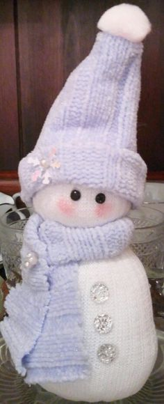 Adorable blue, silver and white snow baby, made of sweater fabric, new sock, pearl pins, snowflake sequin,  pom pom, batting, heavy gauge wire, glue, and jeweled eyes and buttons.  Measures 10 inches high.  Keep out of reach of children and pets, protected from moisture and direct sunlight.  $10