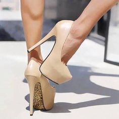Nude colored Heels with leopard print on the bottom.