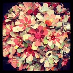 Paper Flowers!   Use Punch or Cricut to cut out 3 different sized flowers.    Poke Metal Brad through the center of paper flowers to fasten together.    Hot Glue button to Metal Brad.    Hot Glue Flower to Paper Lantern or Metal Wreath.    Attach Ribbon to hang!    Voila!