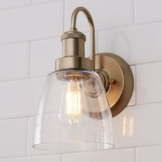 This versatile bath sconce eases into a traditional or transitional bathroom theme.  Its delicate body is simple and clean, pairing well with the clear seeded glass shade.