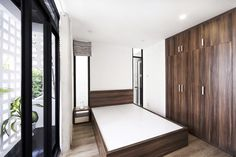 Tight space with timber flooring and timber wardrobe, with access to a small garden