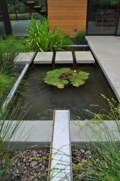 Floating stepping slabs act as a walkway over the feature, while a  water rill spills into the water.