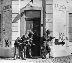 October 1944: A three man combat patrol scouts out the Belgian town of Thimister in advance of the main US force's arrival. A sign on the building behind them indicates the direction of Aachen and Verviers. (Photo by PNA Rota/Getty Images)
