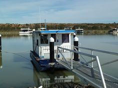 Small 2 berth houseboat permanently moored in the Mannum Waters Residential Houseboat Marina on the Murray River in South Australia. Doesn't get much smaller than this little houseboat