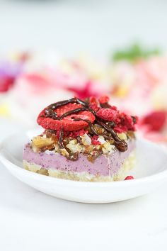 Raw Love Spell Slice Recipe by @J O Mosley Kitchen - white chocolate, macadamia, berry and lucuma slice, infused with flower essences, topped with a raw activated nut crumble, a lavish of chocolate sauce, and a dusting of freeze dried strawberries.