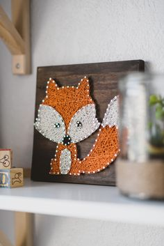 String art woodland fox creature purchased from Etsy from our woodland adventure themed nursery in grey, white, orange, and mint.