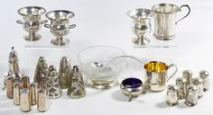 """Lot 106: Sterling Silver Hollowware Assortment; Including (3) cigarette holders, a baby cup with gold washed interior, a cup, (6) matching shakers, (6) Mexico matching shakers, a single shaker as well as an etched clear glass bowl having a sterling foot and spoon, a salt cellar having a blue glass liner and silver spoon and (4) glass shakers having silver overlay; all marked """"sterling"""" or """"925"""""""