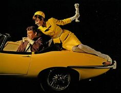 The actor Peter O'Toole photographed with the actress Audrey Hepburn (into a Jaguar XKE convertible, yellow) by Douglas Kirkland