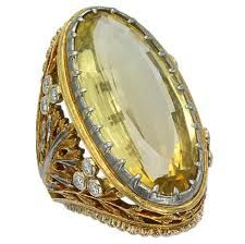 Buccellati ring with 22k yellow gold and rose gold filligree. Gold bezel set around stone with smaller decorative platinum band against the stone. Other smaller bezel set diamonds set in leaves.