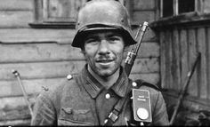 Eastern Front: German rifleman smiles for the camera. Note what looks like a torch hanging from the man's webbing.