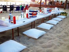 Casual beach wedding reception with pillows on the sand instead of chairs. Clambake OC, Southern California Wedding Caterer