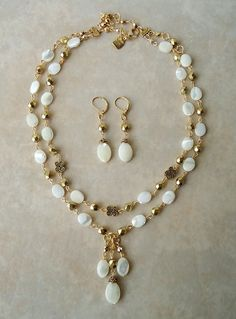 This stunning double-strand necklace combines luminous antique white mother of pearl with bevel-cut gold foiled Austrian crystals accented with 24 karat gold plated pewter beads. This piece is finished with a simple lobster claw closure and has my signature logo tag. This necklace