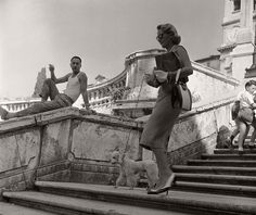 Semiotic apocalypse:An Italian man watches an American tourist walking her poodle down the Spanish Steps in Rome. Circa 1955