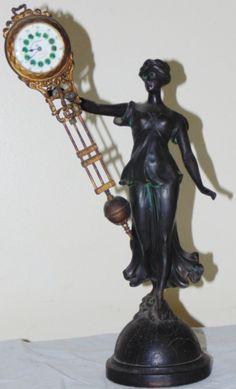Escultura em petit bronze sustentando relógio da marca EGALITAS. Mostrador esmaltado.