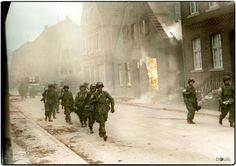 Troops of the 17th U.S. Airborne Division, First Allied Airborne Army, march past a blazing building in Appelhülsen, Germany, as they advance toward the city of Munster, nine miles to the northeast. First Allied Airborne Army troops landed east of the Rhine river March 24, 1945