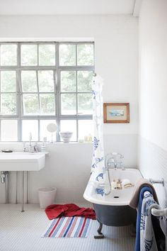 Rather than the more common use of mosaic tiles in a shower or on a feature wall, this bathroom sees them used on the floor and continued halfway up the wall. The design touch has a utilitarian feel that fits perfectly with the gorgeous industrial style windows and grey free-standing bath.