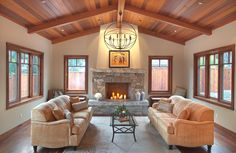 "Isabella great room: western red cedar tongue & groove ceiling, eastern walnut floor and windows. Wall color ""Sedate Gray"" by Sherwin-Williams. Restoration Hardware ""Foucault's pendant"" in iron, large. Custom woodburning stone fireplace designed by Av Elva Sol, solid blueschist hearth and mantel. Soapstone slab fireplace interior. Masonry by Kurt Cook. Staged furniture and art. Ceiling, trim and GC by Buck Construction. Architecture by Holdren+Lietzke."