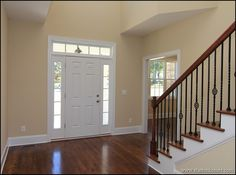 Hardwood staircase with wrought iron balusters and oak handrail.