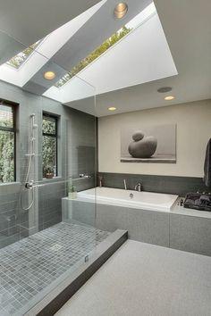 salle de bains grise, une grande cabine de douche et baignoire encastrée