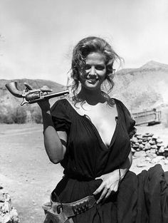 "Italian actress Claudia Cardinale is pictured at the set in a scene of Sergio Leone's epic ""Once Upon a Time in the West"" leisurely holding a…"