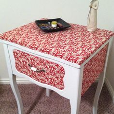 Old sewing machine table from DI, sanded down, repainted, used fusible web to stick fabric to top and sides and then replaced old handle for a new cute one