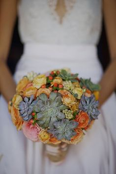The bridal bouquet was created with succulents, ambiance roses, ranunculus, tuberose, garden roses and coffee bean berries in shades of coral, peach, pina colada and teal green.