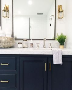 Bathroom with navy cabinets, marble countertops, and gold light fixtures and pulls