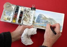Watercolor setup in action, with the paint box clipped to the left side of the watercolor book.