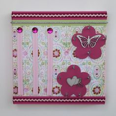 Canvas hair clip board with chipboard embellishment. Hooks for bobbles or headbands to insert on chip shape or from canvas at bottom of frame