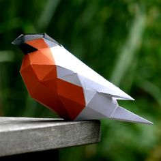 Low-polygon sculpture of a bullfinch made from paper. Build one yourself: Free PDF template included.