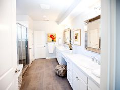 Double vanities span the wall in this large master bath. The bathroom is white, with pops of color added through tasteful accessories and artwork.