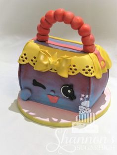 """Shopkins' """"Handbag Harriet"""" fondant covered 3D sculpted cake. Chocolate cake with cookies n' cream buttercream filling."""