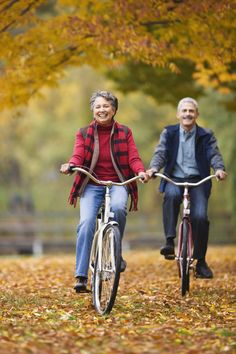 African couple riding bicycles in park in autumn by Gable Denims on 500px