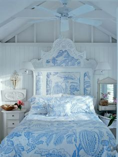 An ornate wooden headboard fits in with cottage decor when it's painted white and upholstered with a softly patterned chic. #bedroom #cottage #blue