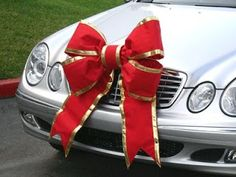 Tie a big bow on your car for a simple Christmas car decoration. Shared by CarDecor.com.