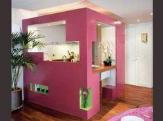 Installée dans le séjour, la petite cuisine s'expose au regard dans un écrin ajouré et coloré en MDF.