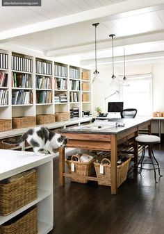 Work / craft room, with large table for multiple people in the center, storage & wraparound desk on the walls.