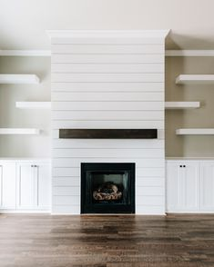 Modern rustic white shiplap fireplace featuring dark stained floating mantle, dark hardwood flooring, custom shaker cabinetry, and floating contemporary shelves Fireplace Feature Wall, Basement Fireplace, Fireplace Shelves, Fireplace Built Ins, Shiplap Fireplace, White Fireplace, Farmhouse Fireplace, Fireplace Remodel, Modern Fireplace